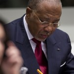 Former Liberian President Charles Taylor takes notes as he waits for the start of Thursday's hearing.
